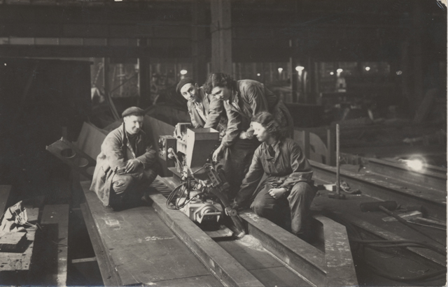 Black and white photograph of 2 women workers and 2 male workers welding HMS Acheron's Bulkhead