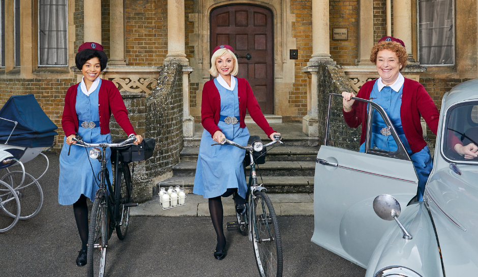 Three midwives in blue dresses and red cardigans. Two midwives holding bikes, one midwife standing next to a car