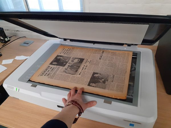 Hand laying a newspaper on an image scanner