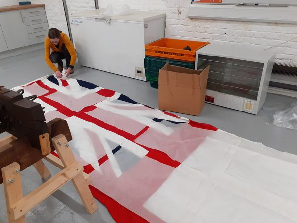 Helen padding a large union flag which is laid out on the floor