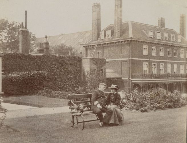 Black and white photograph of a male and female sat on a bench on a formal lawn in front of a Georgian house.
