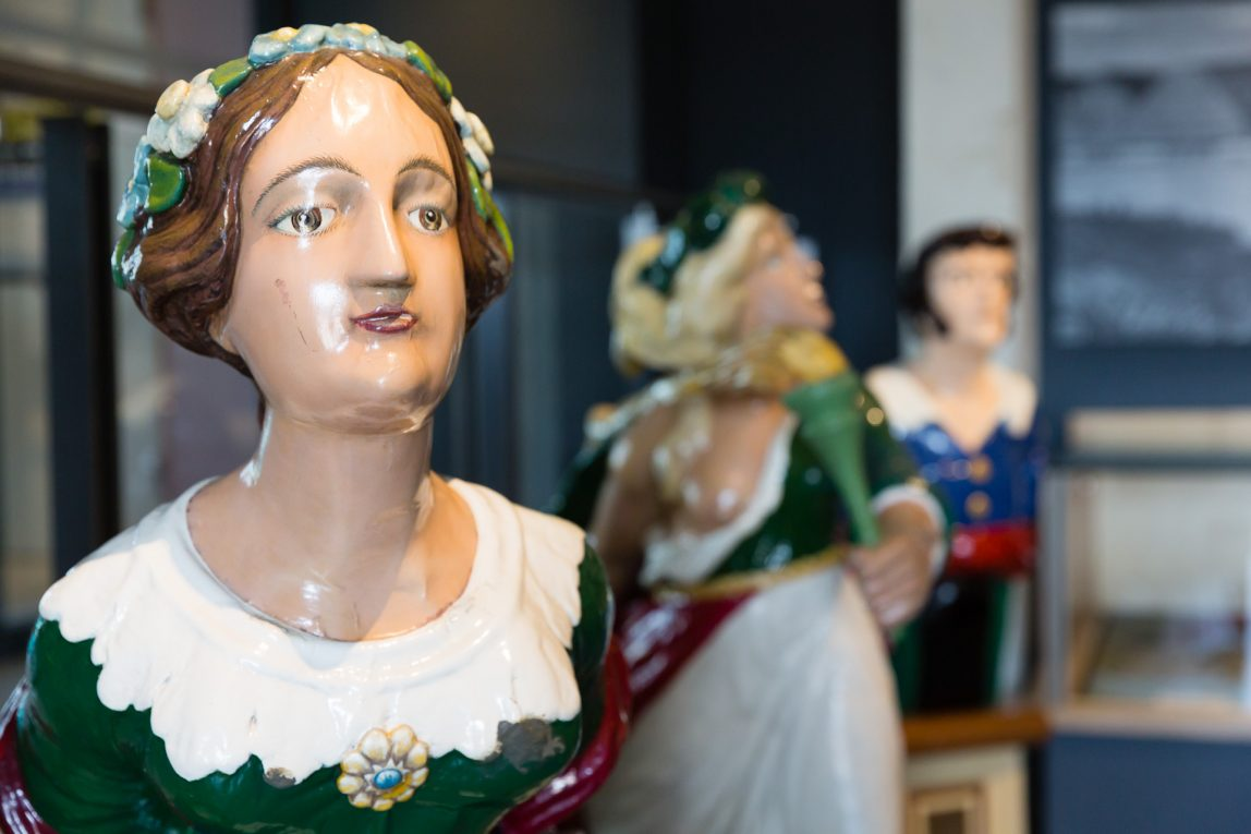 Female figurehead with brown hair and green dress with a white collar