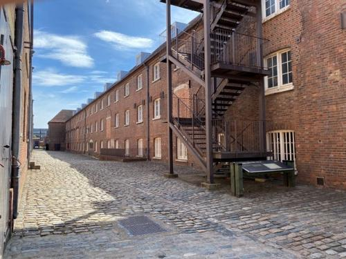 Victorian buildings and cobbled streets with metal external stairway or fire escape at The Historic Dockyard Chatham
